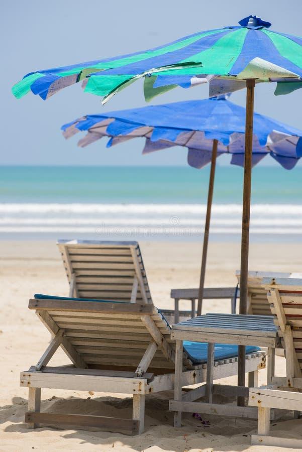 Ligstoel met kleurrijke paraplu stock afbeeldingen