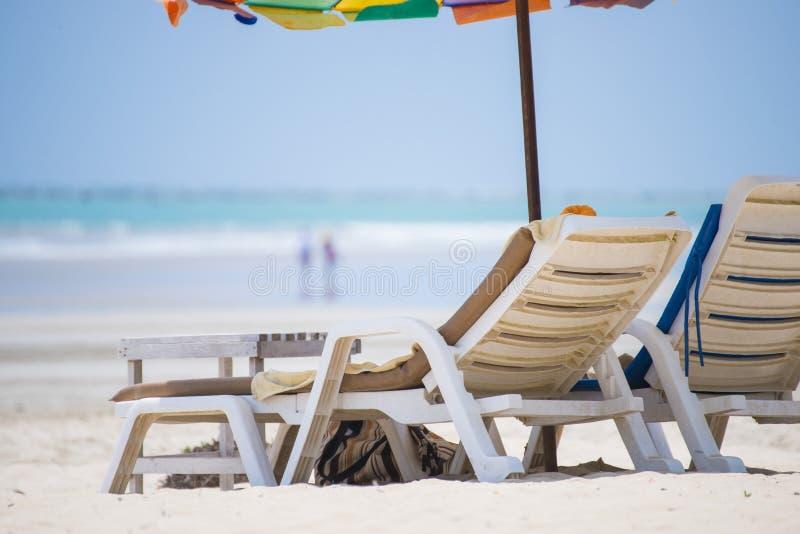 Ligstoel met kleurrijke paraplu stock afbeelding