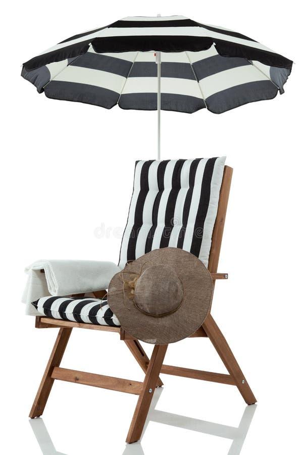 Ligstoel met paraplu, handdoek en sunhat royalty-vrije stock fotografie