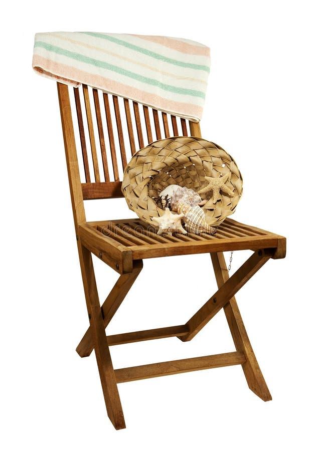 Ligstoel met zonhoed, handdoek en zeeschelpen royalty-vrije stock afbeelding
