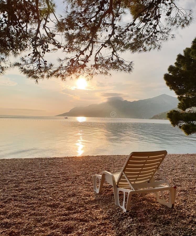 Ligstoel op een kiezelsteenstrand tegen de achtergrond van een kalme schone overzees, bergen en zonsondergang Op zee de zomervaka stock afbeelding