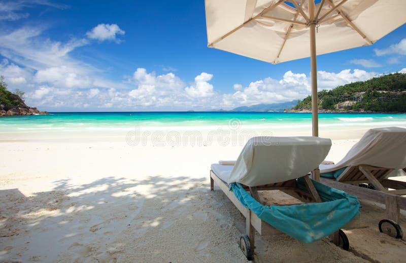 Ligstoel op tropisch strand royalty-vrije stock afbeeldingen