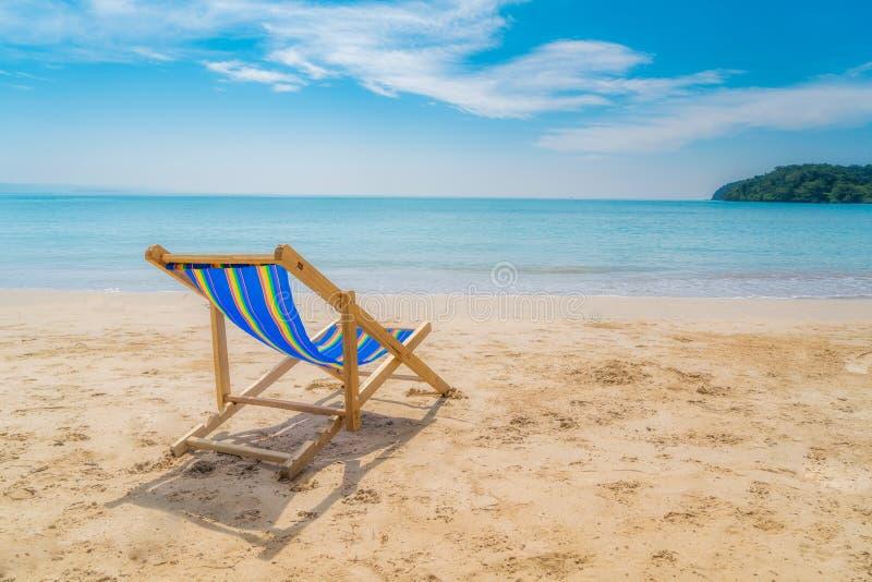Ligstoelen één op het witte zand met blauwe hemel en de zomer overzeese achtergrond De zomer, Vakantie, Reis en Vakantieconcept royalty-vrije stock fotografie