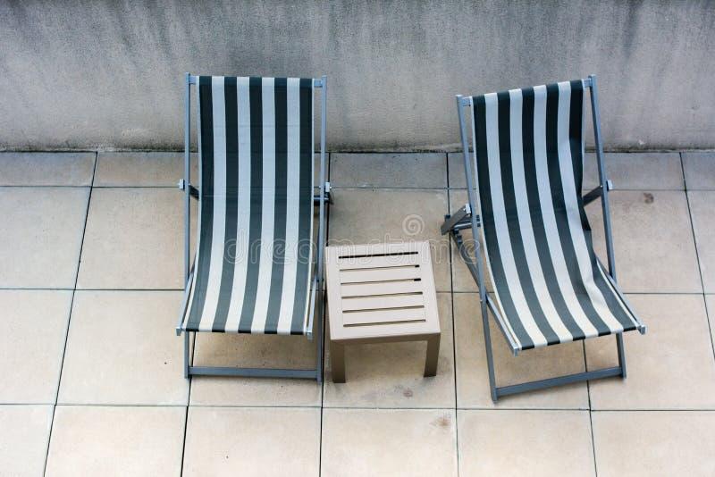 Ligstoelen en klein lijst dichtbij Zwembad stock fotografie