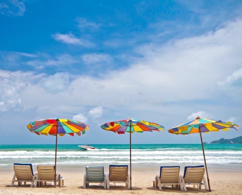 Ligstoelen en kleurrijke paraplu op het strand in Phuket Thaila stock afbeeldingen