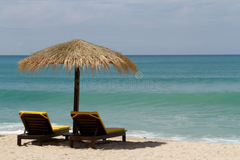 Ligstoelen onder een paraplu naast het overzees stock fotografie