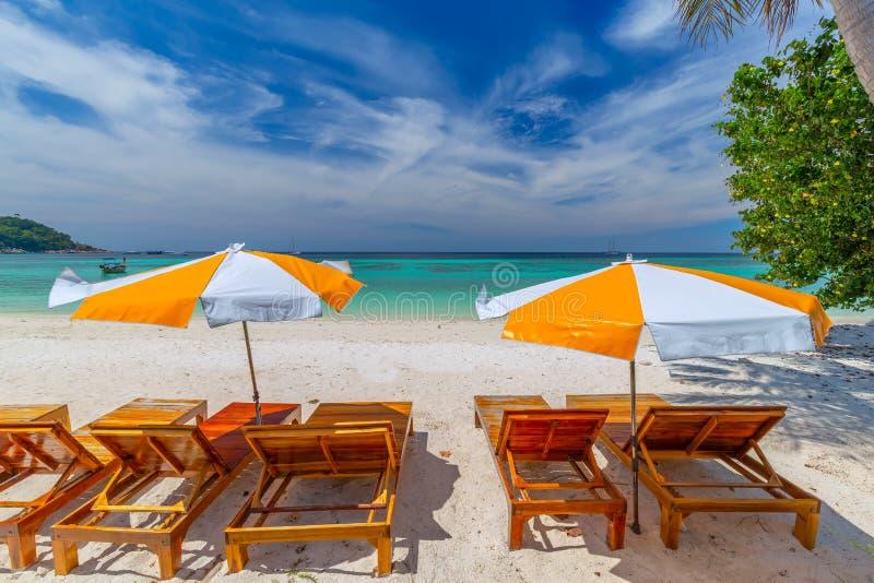 Ligstoelen, paraplu en palmen op het mooie strand voor vakantie en ontspanning bij Koh Lipe-eiland, Thailand royalty-vrije stock afbeelding