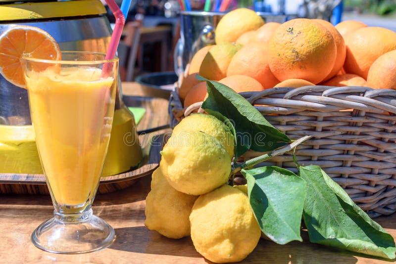 Ligt het vers gedrukte jus d'orange in een glaskop, naast de lijst sinaasappelen en citroenen stock foto's