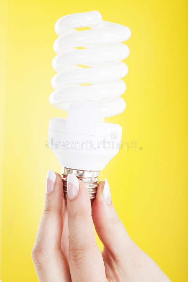 Ligth lamp. Hand holding a lamp on a yellow background royalty free stock photography