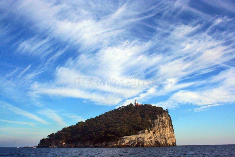 Ligurië: mening van de boot van het Eiland Tino met van overzeese de hemel en de wolken rotsbomen stock fotografie