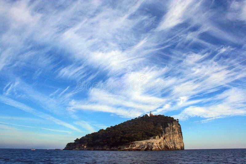Ligurië: mening van de boot van het Eiland Tino met van overzeese de hemel en de wolken rotsbomen stock foto's