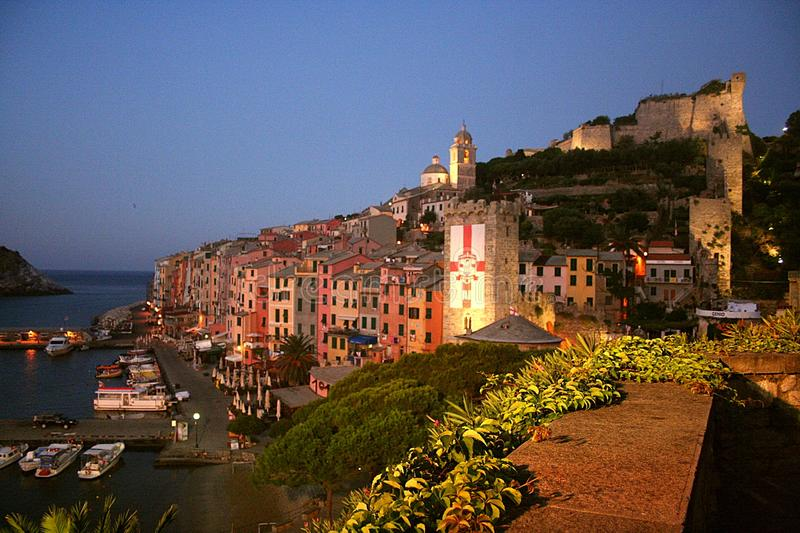 View of colored buildings of Portovenere at dawn with tower, cathedral, cathedral and harbor with moored boats royalty free stock photography