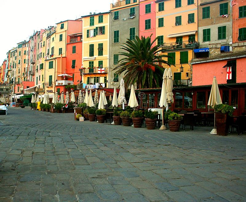View of the colorful buildings with closed windows of Portovenere, a palm tree and cobbled umbrellas closed in front of the enclos. Liguria: View of the colorful stock images