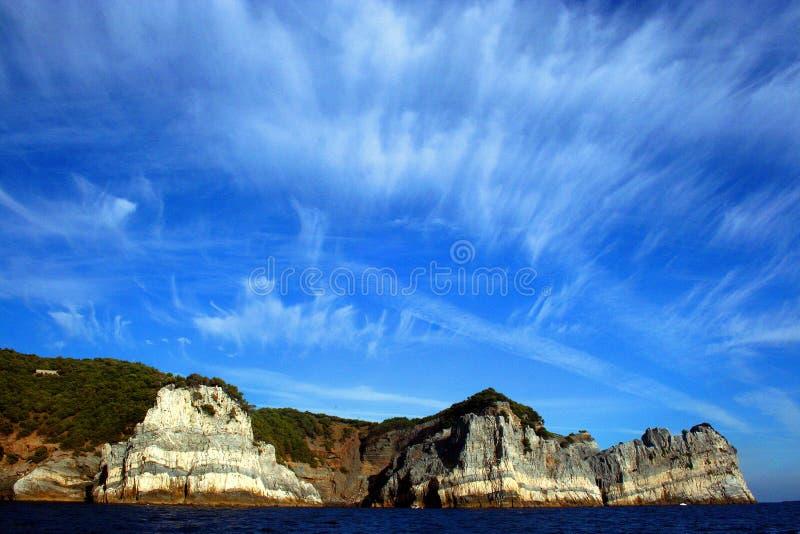 Liguria: visión desde la isla del acantilado de la isla de Palmaria con los árboles cielo y nubes de las rocas imagen de archivo