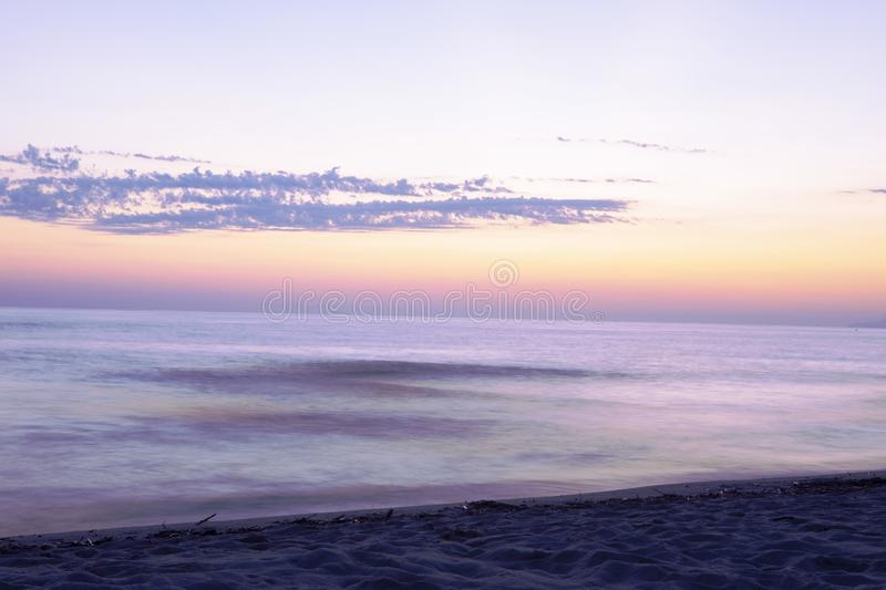 Long exposure sea landscape with  twilight pink purple, orange sky. Seascape with sunset sky and motion blur water. Marina di Torr royalty free stock images