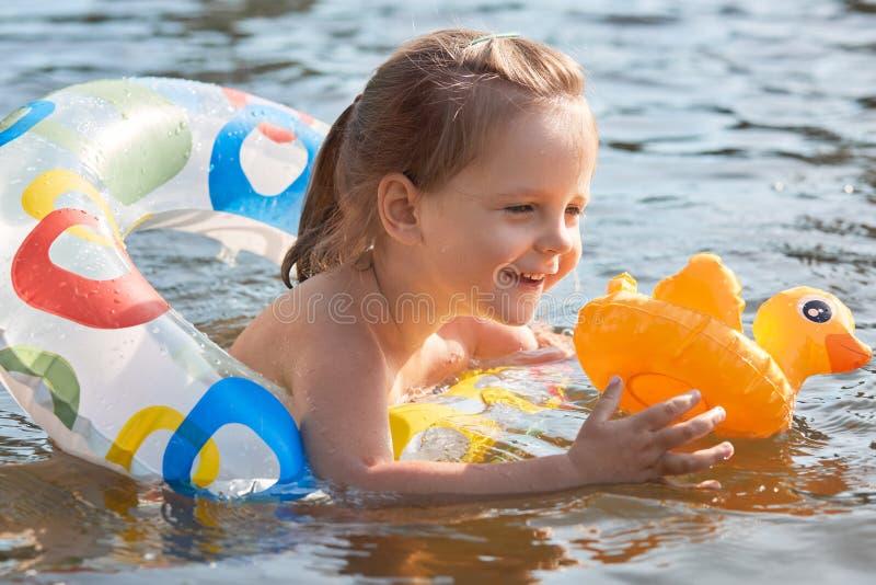 liitl女孩室外射击lifebuoy,愉快的儿童游泳的在池塘,在橡胶环的todler获得乐趣在河,拿着黄色鸭子, 库存图片