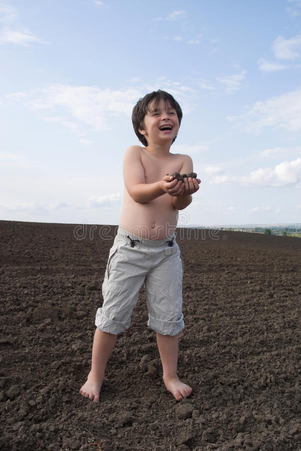 The liitle boy with black earth stock photo