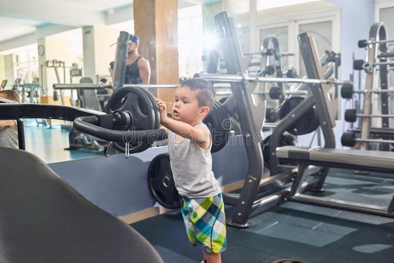 Liitlejongen die zware domoren op metaalsimulator zetten die zich in gymnastiek bevinden royalty-vrije stock foto's