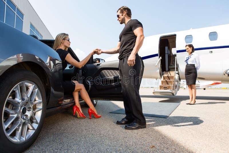 Lijfwacht Helping Elegant Woman die stappen uit royalty-vrije stock foto's