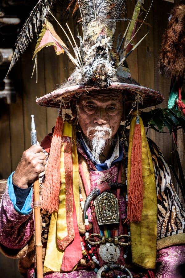 LIJIANG, CHINA - abril 22,2016: O ancião que veste o chinês tradicional veste-se para mostrar turistas em Lijiang foto de stock