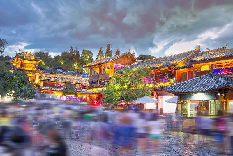 Lijiang gammal stad i aftonen med folkmassaturisten royaltyfri foto