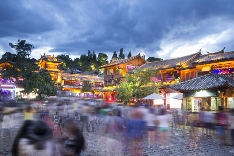 Lijiang gammal stad i aftonen med folkmassaturisten, Kina royaltyfria bilder
