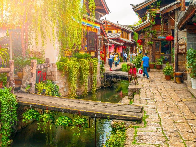 LIJIANG, PROVÍNCIA DE YUNNAN, CHINA - 8 DE SETEMBRO DE 2012: Rua da cidade velha de Lijiang com os canais estreitos da água Mundo imagem de stock