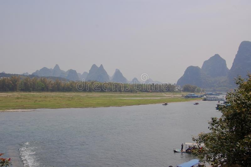 Lijiang River between Guilin and Yangshuo, China with boats cruising down the river with the misty karst mountains stock image
