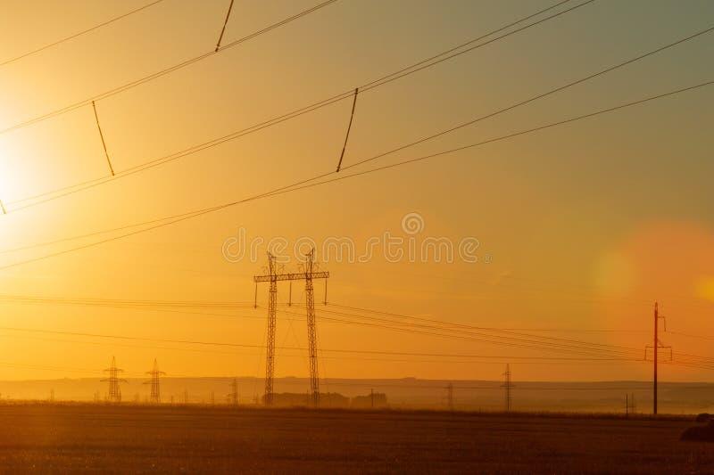 Lijn de met hoog voltage van de machtstransmissie Energiepijlers Bij zonsondergang, stock afbeelding