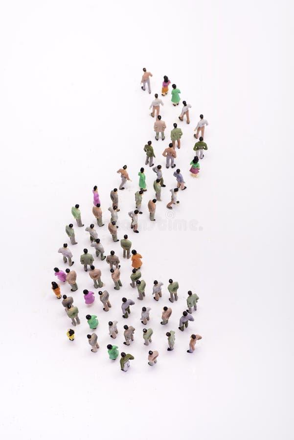 Lijn van miniatuurmensenmening van hierboven, over wit stock fotografie