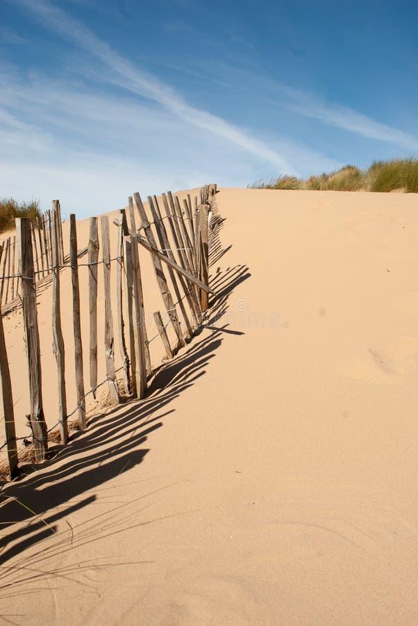 Lijn van oude omheining op een strand met horizontale schaduwen royalty-vrije stock afbeeldingen