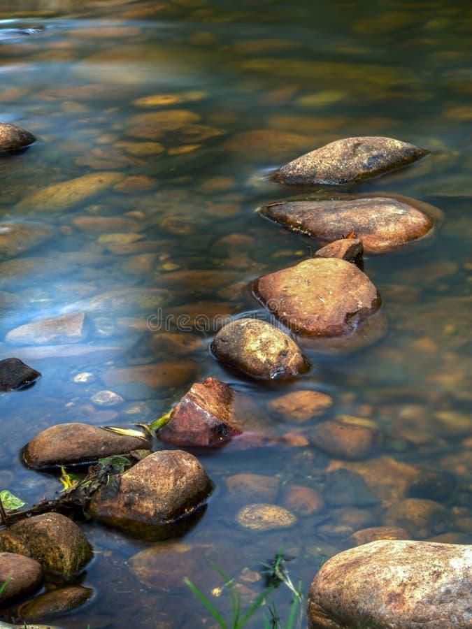 Lijn van rotsen in een vijver stock afbeeldingen
