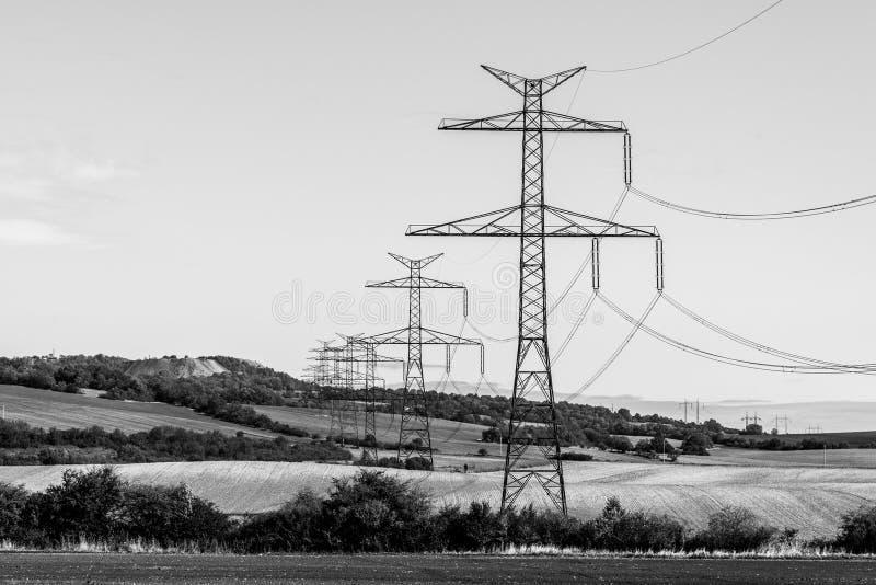 Lijn van transmissietorens, of elektriciteitspylonen, in het landelijke landschap stock fotografie