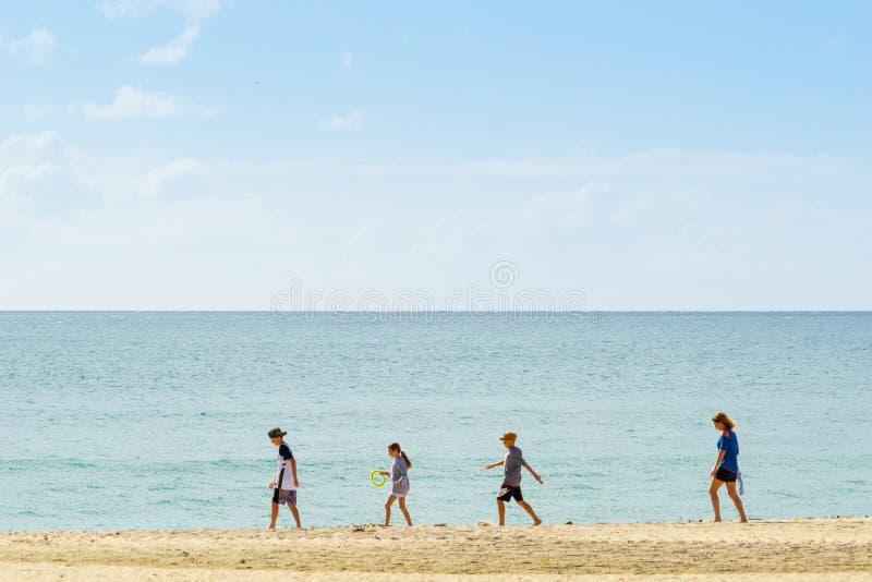 Lijn van vier mensen die in afstand langs waterenrand lopen stock fotografie