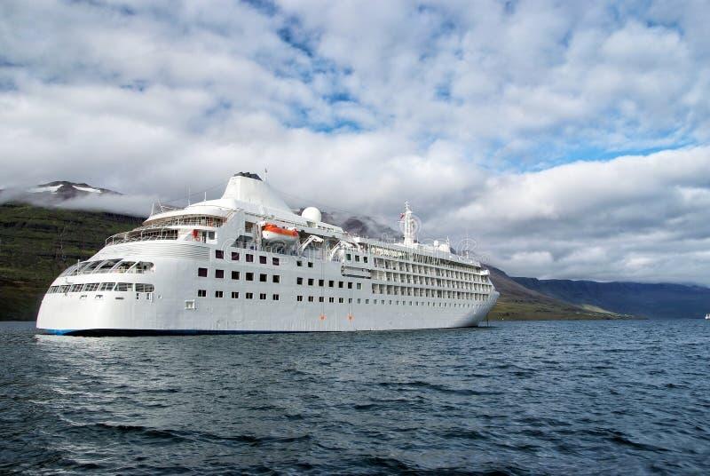 Lijnboot in overzees op berglandschap in Sejdisfjordur, IJsland Cruiseschip in overzees met bergen op bewolkte hemel stock fotografie