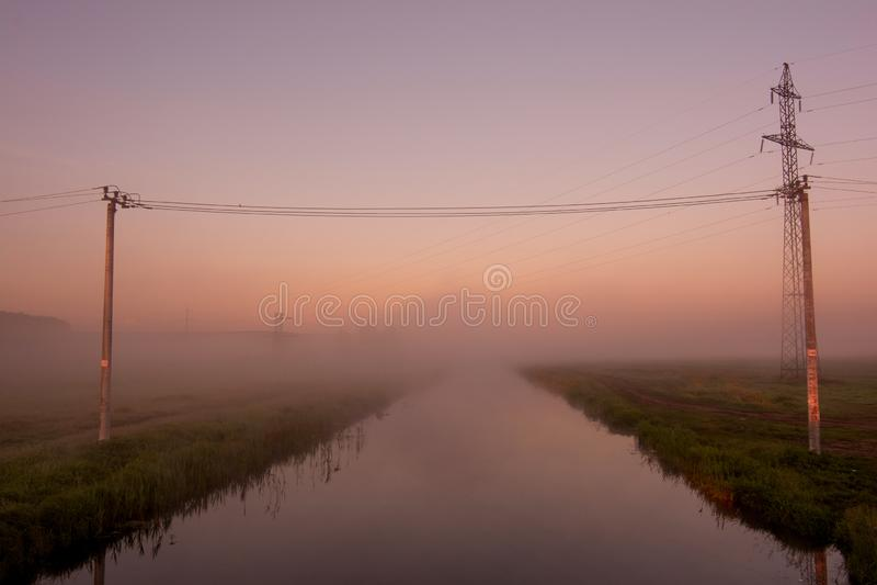 Lijnen de met hoog voltage van de steunenmacht over de rivier tegen de hemel op zonsopgang De elektro industrie stock afbeeldingen