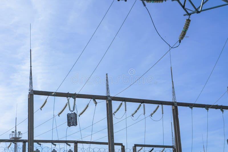 Lijnen de met hoog voltage van de steunenmacht tegen de blauwe hemel met wolken De elektro industrie royalty-vrije stock afbeeldingen