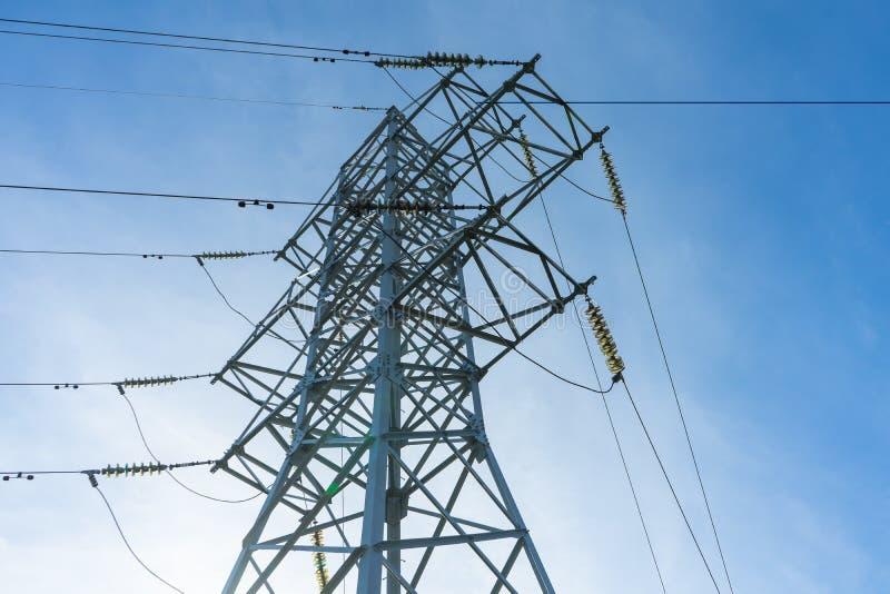 Lijnen de met hoog voltage van de steunenmacht tegen de blauwe hemel met wolken De elektro industrie royalty-vrije stock fotografie