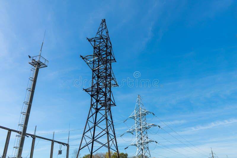 Lijnen de met hoog voltage van de steunenmacht tegen de blauwe hemel met wolken De elektro industrie stock fotografie