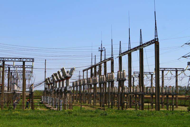 Lijnen van de stroompost en transformatorblokken de met hoog voltage op een blauwe hemel royalty-vrije stock afbeeldingen