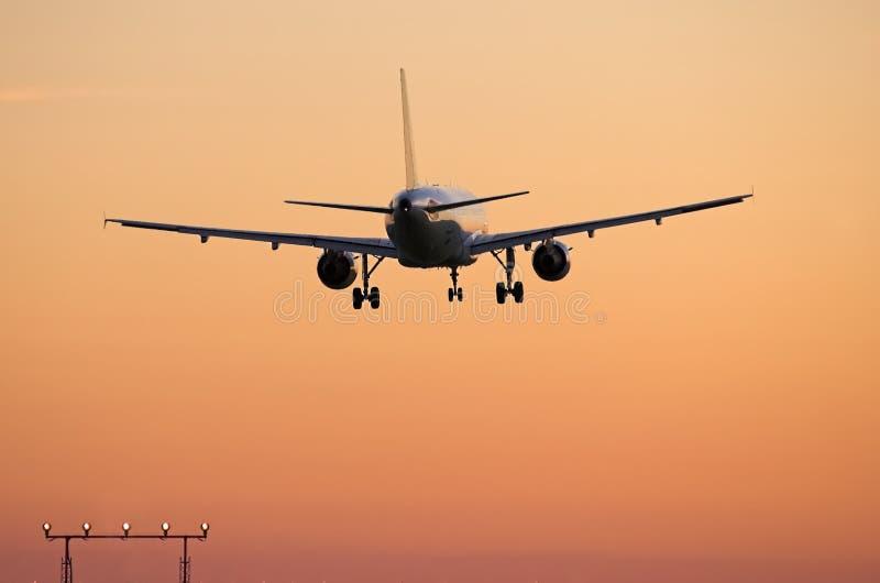 Lijnvliegtuig dat bij zonsondergang landt royalty-vrije stock foto