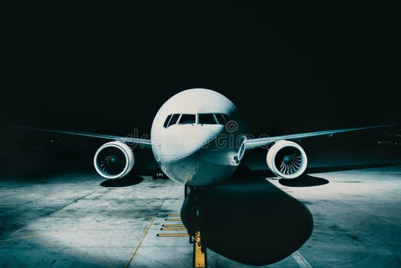 Lijnvliegtuigvliegtuig bij de eindmening van de voorcockpitfuselage, op baan bij nacht wordt geparkeerd die stock foto