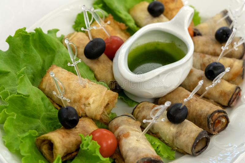 Lijst die in een restaurant plaatsen Koude snacks Gebraden courgettebroodjes met olijven en tomaten op slabladeren Groene saus en royalty-vrije stock foto's