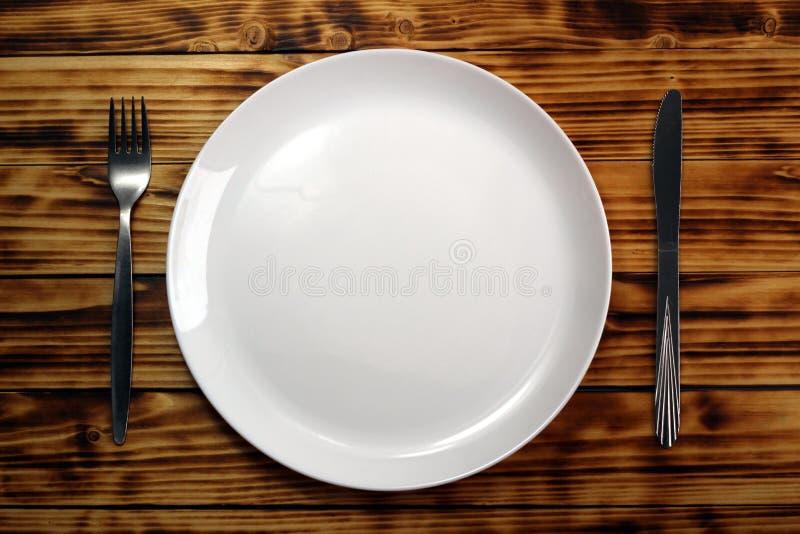 Lijst die met een plaat, een vork en een mes plaatsen Witte lege plaat, zilveren vork en mes op een donkere houten achtergrond stock fotografie