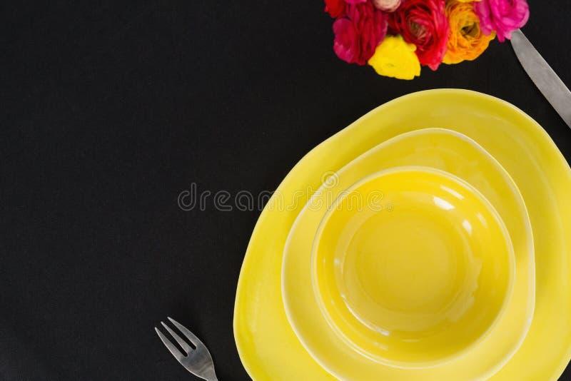 Lijst die met gele kom en platen plaatsen stock foto
