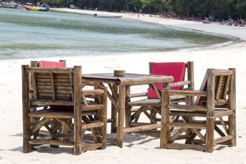 Lijst en bamboestoelen in tropisch strand naast het overzees, Thailand Sluit omhoog stock foto