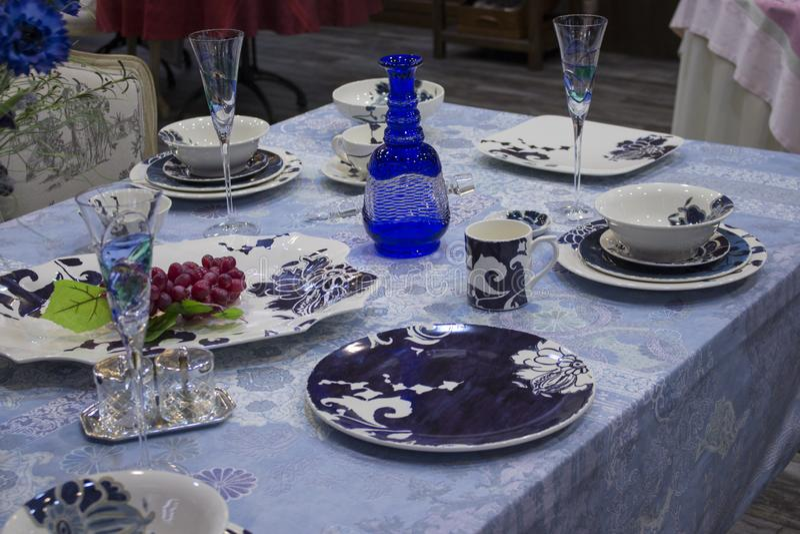 Lijst het plaatsen, donkerblauwe platen, een blauw tafelkleed en een karaf blauw glas Partij van het ontwerp de dienende restaura stock fotografie