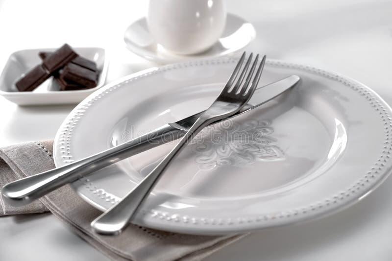 Lijst het plaatsen mes en vork op porseleinplaat, linnendoek, kom van chocoladestukken en kop met schotel op witte achtergrond stock foto's