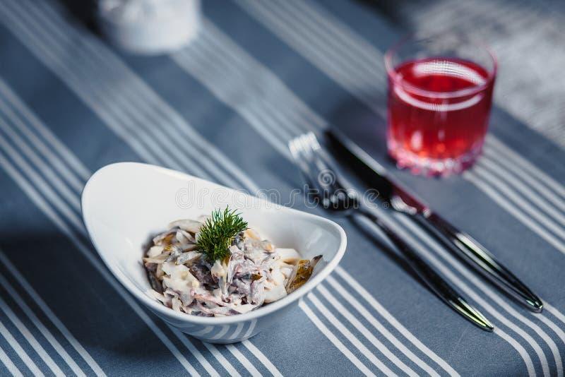 Lijst in het restaurant Op de lijst is een salade in een witte plaat, een mes, een vork, een glas met rood sap Op de lijst stock foto