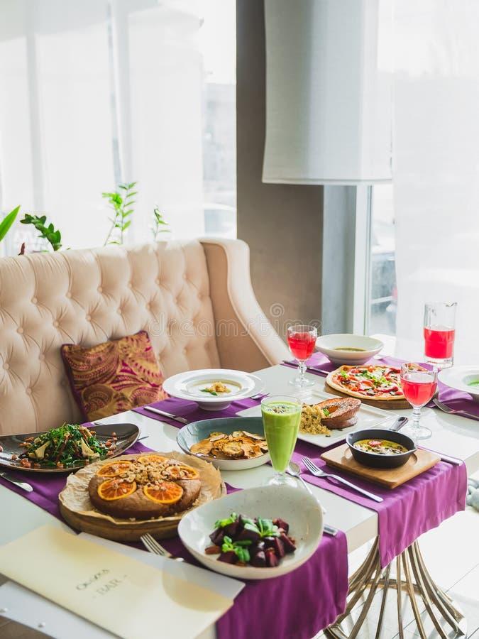 Lijst met vegetarische schotels - pizza met groenten, salades, pastei en verse zoete dranken royalty-vrije stock foto's